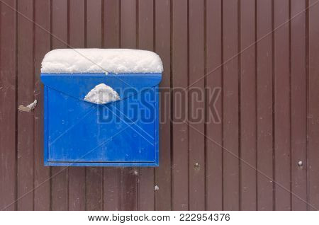 A blue metal mailbox on a brown fence. On the mailbox is a layer of snow. Background. Structure.