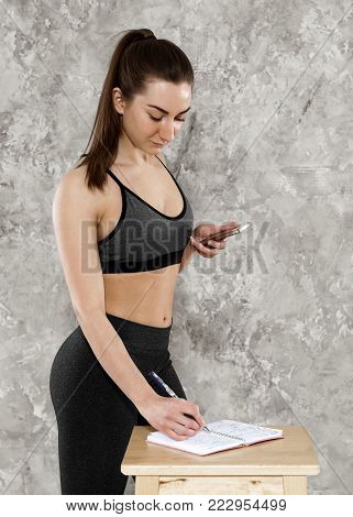 athletic young brunette girl exercising at home exercising and diary of nutrition and exercise
