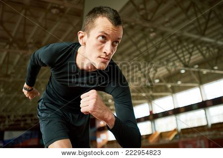 Motivational portrait of young athlete ready to start  on running track in modern indoor stadium, copy space