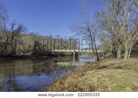 Brandywine Creek in Wilmington, Delaware with a bright blue sky and reflections in the water looking toward Thompsons Bridge
