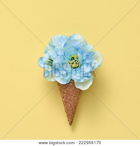 Ice Cream Cone with Bouquet of Flowers. Trendy fashion Style. Spring Summer Floral concept. Creative Minima on Yellow. Blue Flower, Vanilla Color. Art Vintage