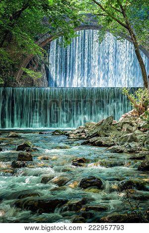 Beautiful old stone bridge between two waterfalls in Paleokaria, Trikala Greece