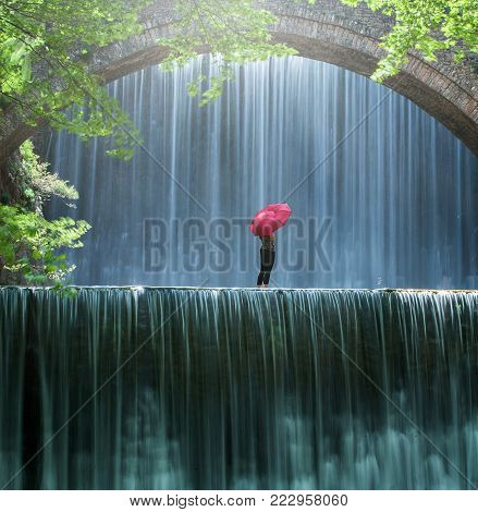 Young woman standing in the creek with a red umbrella between two waterfalls and looks at the falling water