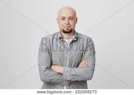 Bald handsome man with beard and crossed hands standing over white background. Person in casual clothes waiting in queue to order cup of coffee and brighten up his morning. Emotions concept