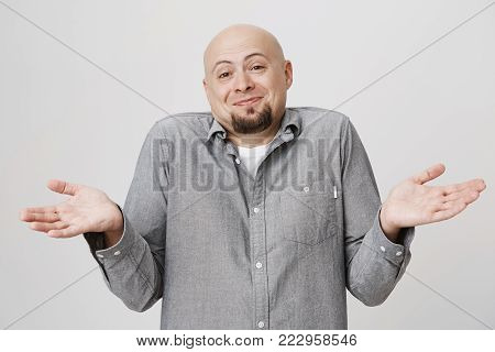 Emotions and body language concept. Good looking happy bald man with beard shrugging and over white wall. Male is perplexed but looks to be in good mood. Feeling glad he is not involved. Copy space