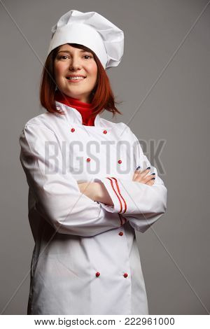Image of cook girl in white robe and cap with crossed hands on waist