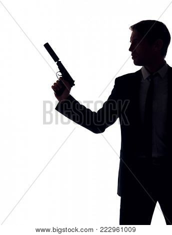 Silhouette of guy in business suit with gun at hand