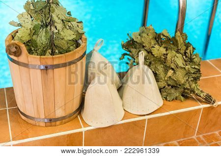 culture, spa, weekends concept. close up of obligatory equipment for having steam bath in russian traditions, this set includes three hats for friends, brooms and bucket of cold water