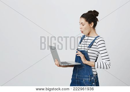 Profile of excited amazed caucasian brunette female copywriter with two hairbuns in denim clothes working on modern generic laptop computer. Young woman reading e-mails, looking at screen with excitement