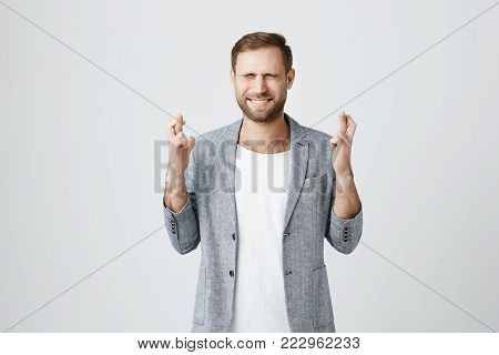 Handsome stylish bearded male entrepreneur with trendy haircut standing against gray background with crossed fingers and closed eyes, frowning his face, having pleading expression asking for good luck at his new project