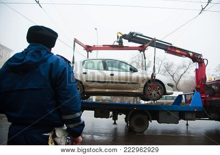 Traffic police officers on the street lifting the car on the tow truck for taking away