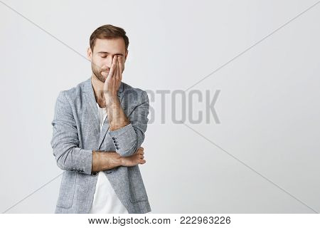 Attractive bearded stylish male wears trendy clothes keeps hand on face, has headache after having conference, tired after hard working day, isolated against studio wall. Negative emotions and face expression