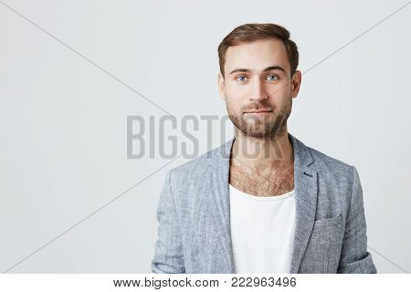 Portrait of serious bearded male wears fashionable clothes, hears attentively something important, isolated against concrete wall. Young male model with thick beard has good mood