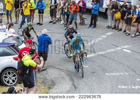 Col du Glandon, France - July 24, 2015: Three cyclists (Scarponi of Astana, Uran of Etixx-Quick-Step and Gautier of Europcar),climbing the road to Col du Glandon in Alps, during the stage 19 of Le Tour de France 2015.