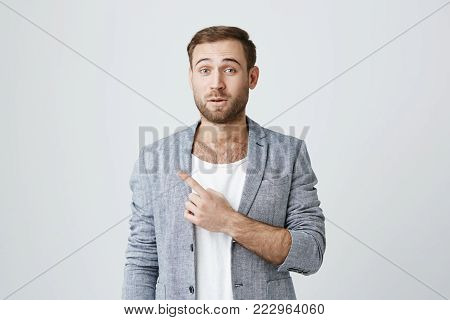 Amazed stunned male model with stubble, wearing gray jacket over white t-shirt, looking with puzzlement and confusion at camera pointing with forefinger at copy space for your text or advertisement