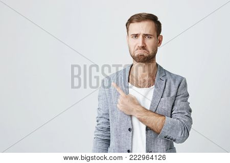 Displeased upset caucasian male model wearing trendy clothes frowning face looking with dissatisfaction at camera, pointing finger at copy space. Caucasian man indicating something on studio wall