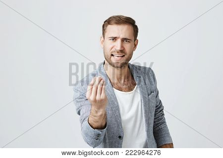 Furious angry displeased young caucasian male with stubble frowns face in displeasure, gestures actively, demonstrates his irritation, annoyed with someone. Negative emotions concept.