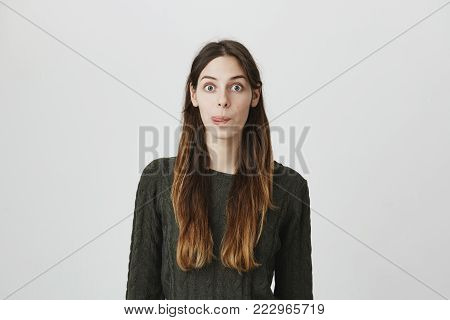 Naughty european girl with dark hair in green sweater misbehaving, sticking out her tongue at camera as a sign of disobedience, protest and disrespect. Human emotions, reactions, feelings and attitude