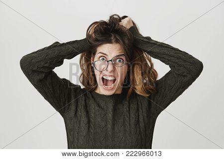 Young european woman in glasses and dark-green trendy sweater, screaming with angry and depressed expression, pulling her hair, isolated over white background. Girl can't stand her dormitory neighbor. Emotions concept