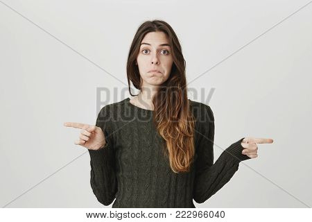 Waist-up portrait of attractive young girl with sad and disappointed expression, pointing index fingers in both sides, isolated over white background. Woman confused, don't know what to do.