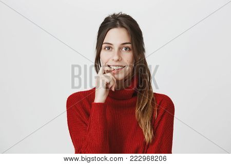 Attractive european female with long brown hair smiling broadly, holding her finger on lower lip over white background looking curious and interested in conversation with handsome young man.