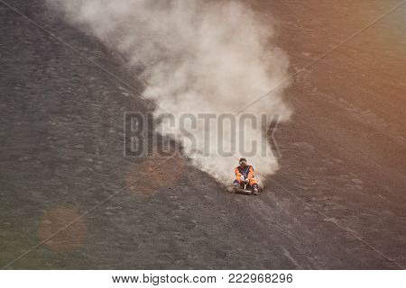 Speed ride on volcano boarding in Nicaragua. Woman descend from volcano