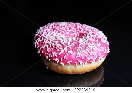 Donut. Beautiful pink donut on black reflective studio background. Isolated black shiny mirror mirrored background for every concept. Food photo.