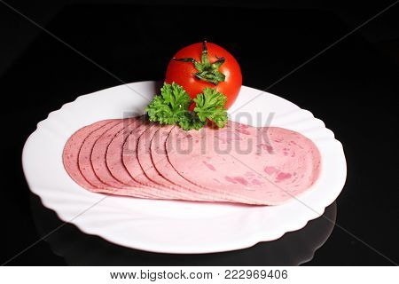 Round ham. Sliced pink ham meat on black reflective studio background. Isolated black shiny mirror mirrored background for every concept. Food photo.