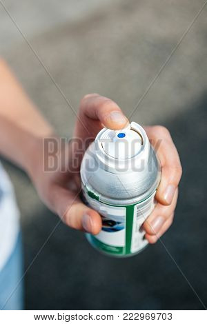 Woman hand holding high-pressure bottle can of graffiti paint or other gas as pepper security gas