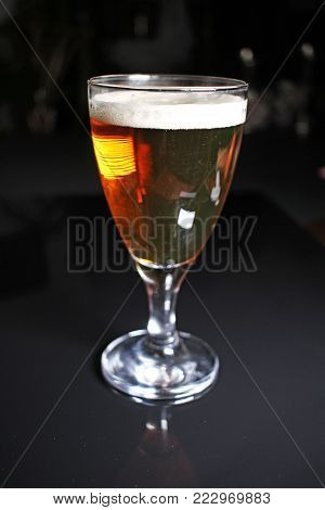 Beer. Light yellow golden beer with glass on black reflective studio background. Isolated black shiny mirror mirrored background for every concept. Beer.