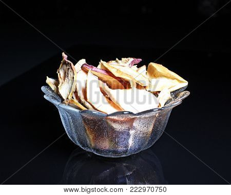 Apple slices. Dry dried apple chips on black reflective studio background. Isolated black shiny mirror mirrored background for every concept. Apple chips.