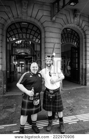 LUXEMBOURG - JUN 5, 2016: Penicuik Tartan Army - Scotland national footbal team members fan smiling posing a beer front Luxembourg central Train station - fans of the Scotland national football team