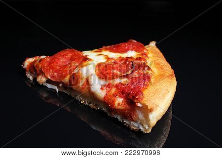 Pizza. Pizza slice on black reflective studio background. Isolated black shiny mirror mirrored background for every concept. Pizza slice.