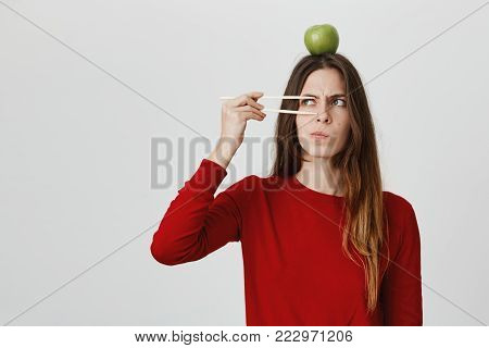 Studio shot of emotional clueless young female with long hair dressed in red sweater with green apple on her head having dissatisfied puzzled look, frowning face in displeasure. Human emotions, feelings and face expression