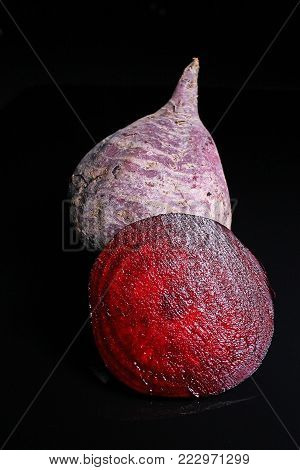Beet beetroot. Whole and half cutted beet beetroot on black reflective studio background. Isolated black shiny mirror mirrored background for every concept. Beetroot.