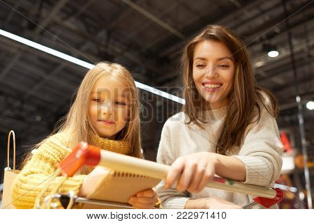 Portrait of cheerful young woman grocery shopping with daughter in supermarket reading shopping list and leaning on cart