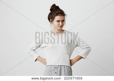 Portrait of irritated and dissatisfied brunette girl with hairbun and oval face, dark eyes, wearing loose casual sweater, frowning her eyebrows, standing with arms akimbo, being displeased with parent s words