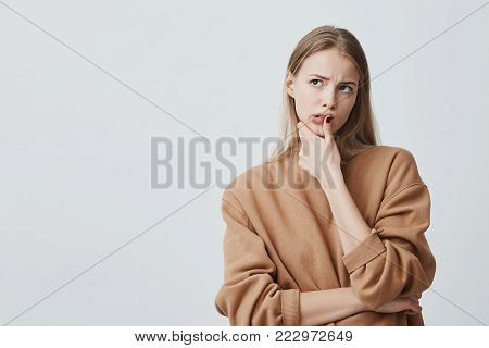 Indoor shot of thoughtful beautiful woman with long blonde hair, looks upwards with pensive expressions, plans something, poses against blank wall. Serious concentrated female keeping finger on chin