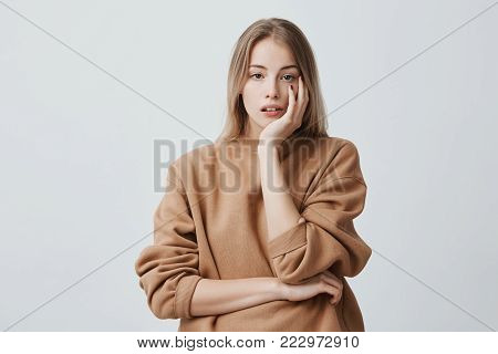 Indoor shot of thoughtful pretty woman with long blonde hair, looks at camera with pensive expressions, plans something on coming weekends, poses against blank wall. Dreamful female