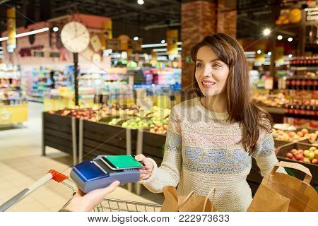 Portrait of beautiful young woman buying groceries in supermarket smiling happily while paying with NFC payment via smartphone, copy space