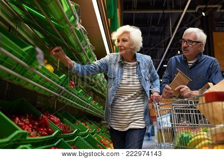 Portrait of modern senior couple with shopping cart  choosing fruits and vegetables in supermarket while enjoying grocery shopping, copy space