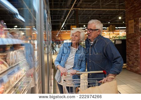 Portrait of modern senior couple grocery shopping in supermarket, smiling happily while choosing frozen foods standing by freezers , copy space
