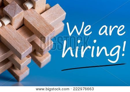 Job recruiting advertisement represented by 'WE ARE HIRING' texts on blue background with wooden brain teaser talking about the difficult tasks, new challenges and opportunities.