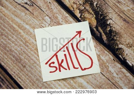Skills written on sticky note on the wooden table or Improve Your skills Concept