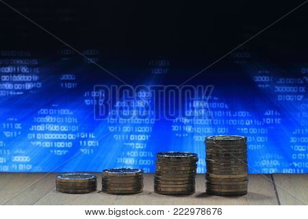 Growing business in safe internet environment. Coin pile stacked into columns of increasing chart shape. Photo of computer screen display with White Binary number.