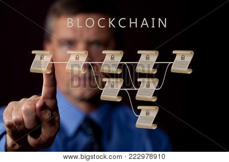 Blockchain schematic on glass panel with senior technology executive pointing with finger at one of the encrypted blocks