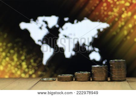 World of idea. Coin pile stacked in increasing chart shape on wood board with White dots grid pattern world map on black and yellow orange glittering dot