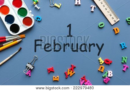February 1st. Day 1 of february month, calendar on schoolboy or schoolgirl table, blue background. Winter time.