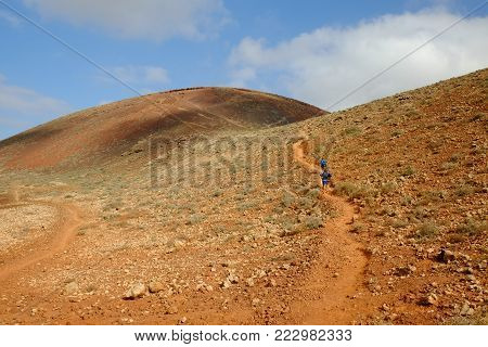 Unrecognised tourists ascending the volcanic mountains of the Canary Island Fuerteventura, Spain.