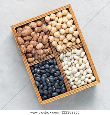 Different kinds of beans: black, pinto, white and chickpeas in a wooden box on concrete background, square format